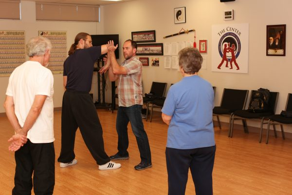 Instructors, Dr. James Fox, PhD and Barbara Wallace watch as Dr. Greg Moore demonstrates Push Hands form with instructor Andew Holmes-Swanson at the Eugene Yang Chengfu Tai Chi Chuan Center.