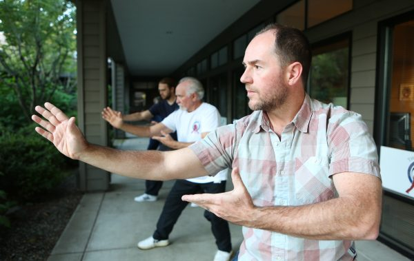 Dr. Greg A. Moore performs Tai Chi stances with his fellow instructors outside the 2017 Eugene Yang Chengfu Tai Chi Chuan Center location.